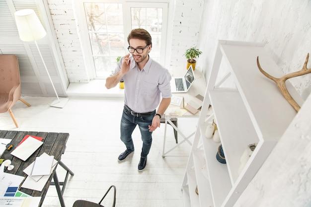 営業する。オフィスに立っている間電話で話している陽気な青年実業家