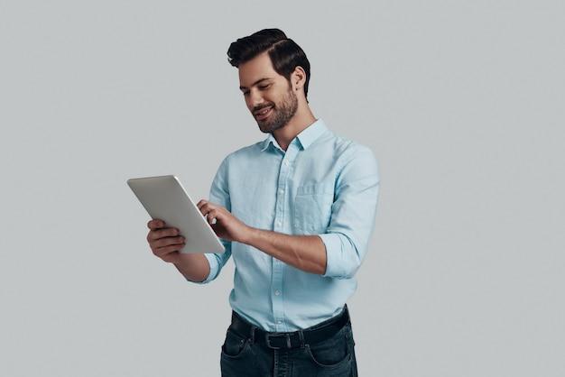 営業する。灰色の背景に立っている間デジタルタブレットを使用して作業しているハンサムな若い男