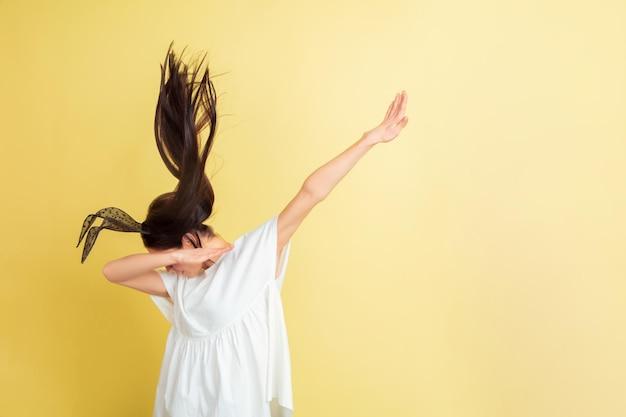 軽くたたく、軽くたたく。黄色のスタジオの背景にイースターバニーとして白人女性。