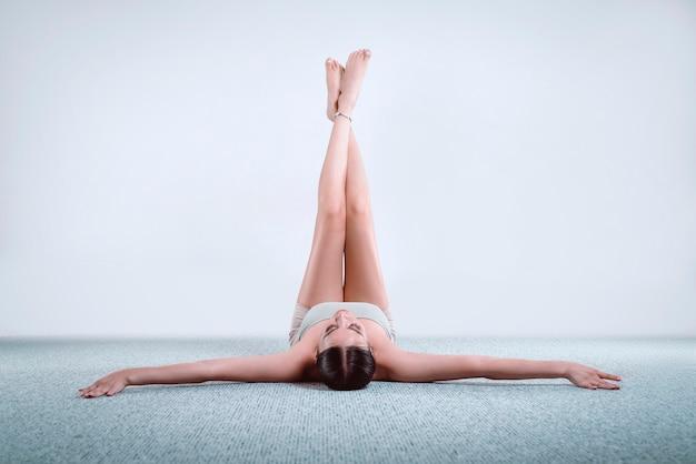 Делать фитнес-упражнения, заниматься йогой в классе, молодая женщина медитирует дома. тренировки, фитнес, внимательность, тренировки, медитация, йога, уход за собой, релаксация, пилатес, концепция здорового образа жизни