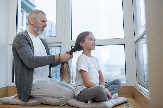 Doing hair. a gray-haired dad doing hair to his daughter