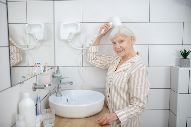 Doing hair. gray-haired woman drying her hair in the bathroom