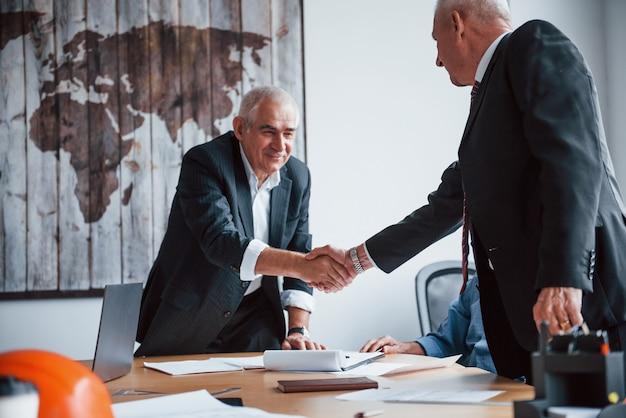 악수를 하고 있습니다. 나이든 사업가 건축가로 구성된 나이 든 팀이 사무실에서 회의를 합니다.