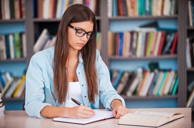 그녀의 숙제를 하고 있다. 도서관 책상에 앉아 있는 동안 메모장에 무언가를 쓰고 책을 읽는 젊은 여성