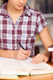 그녀의 숙제를 하고 있습니다. 책상에 앉아 있는 동안 메모장에 무언가를 쓰고 책을 읽는 젊은 여성