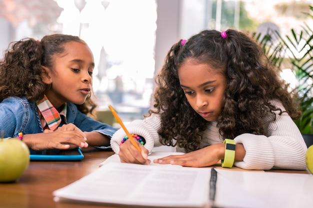 숙제를. 그녀의 숙제를 하 고 노란색 시계를 입고 곱슬 검은 머리여 학생