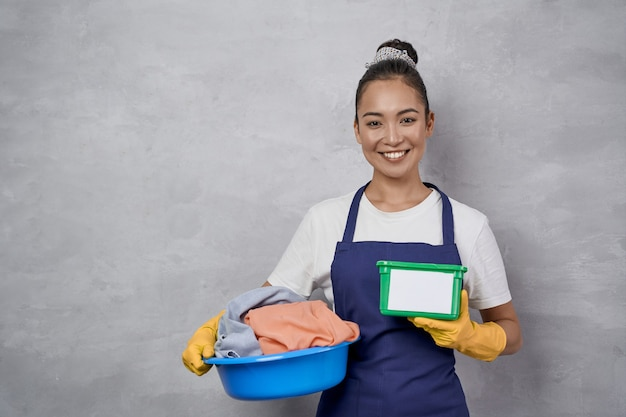 Doing laundry. portrait of happy maid woman in uniform holding basket with laundry and green plastic box with washing capsules, smiling at camera against grey wall. housekeeping, housework