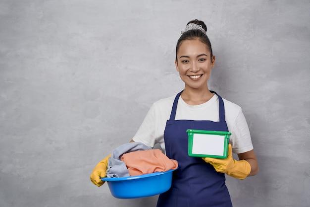 洗濯をする。灰色の壁に対してカメラに微笑んで、洗濯物と洗濯カプセルと緑のプラスチックの箱が付いている制服を保持しているバスケットで幸せなメイドの女性の肖像画。ハウスキーピング、ハウスワーク