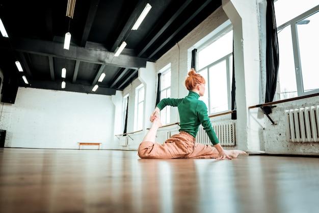 다리 분할하기. 녹색 터틀넥을 입고 빨간 머리를 가진 전문 요가 강사