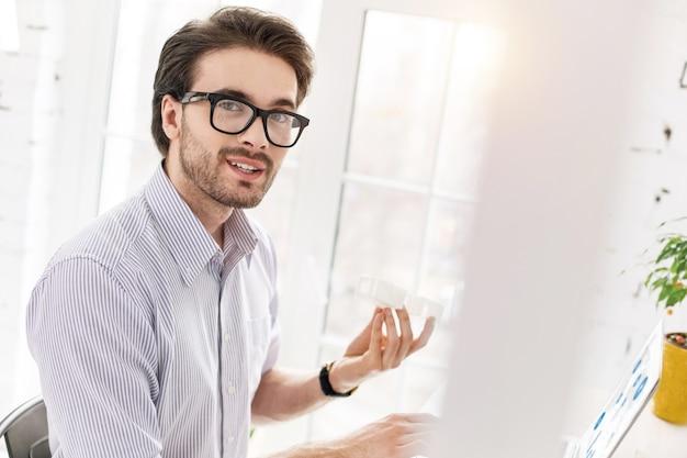 頑張って。テーブルに座って彼のラップトップで作業している熟練したひげを生やしたマネージャー
