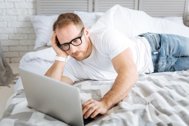 Выполняю свою внештатную работу. харизматичный спортивный очаровательный мужчина, лежащий на кровати и использующий ноутбук, выражая интерес и просматривая интернет