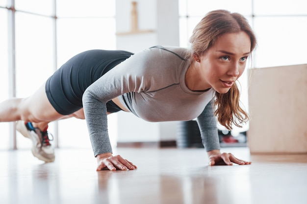 Doing push ups. sportive young woman have fitness day in the gym at morning time