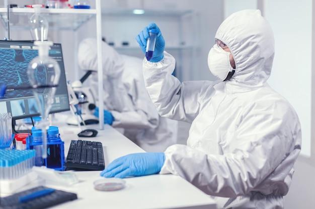 Проведение исследований по поиску вакцины от коронавируса в костюме ppe. ученый в лаборатории в комбинезоне проводит исследования и анализирует вещества во время глобальной пандемии covid19.
