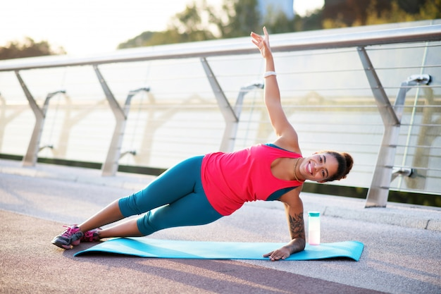 Doing side plank. smiling african-american woman doing side plank while finishing workout
