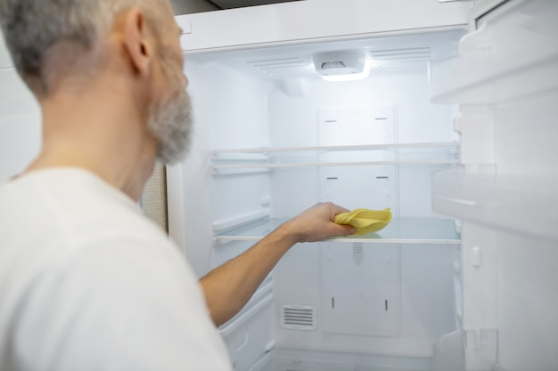 いくつかの掃除をしています。台所の冷蔵庫を掃除している白髪の男