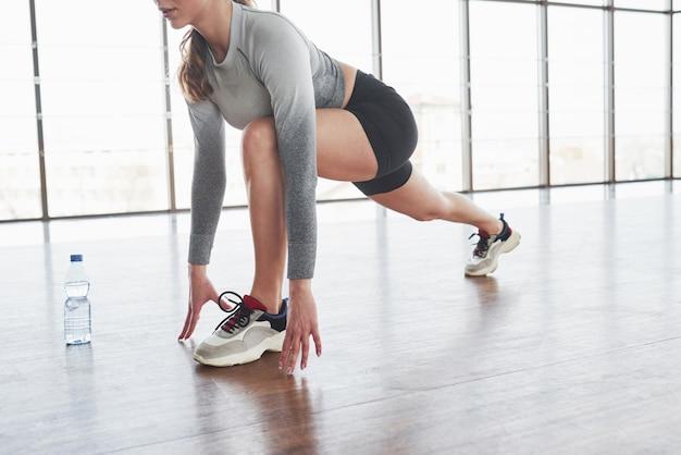 Приседания. спортивная молодая женщина имеет фитнес-день в тренажерном зале в утреннее время