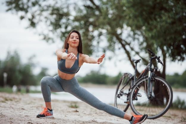 しゃがむこと。良い体の形で女性のサイクリストは、ヨガの練習を行い、昼間にビーチで彼女の自転車の近くでストレッチ