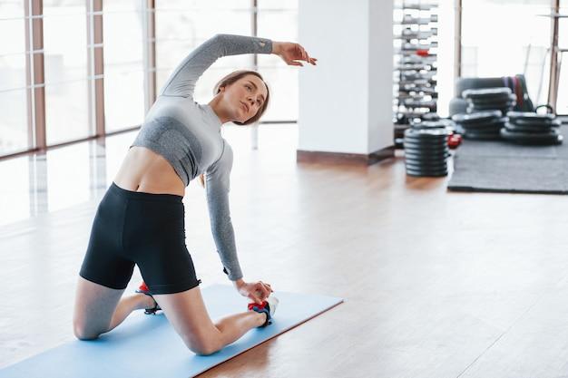 Делаем растяжку. спортивная молодая женщина имеет фитнес-день в тренажерном зале