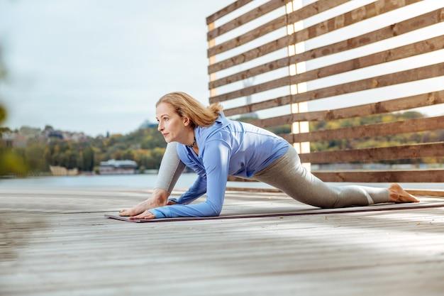 朝の運動の後にストレッチをする。屋外で朝のエクササイズをした後、ストレッチを練習している決心した女性