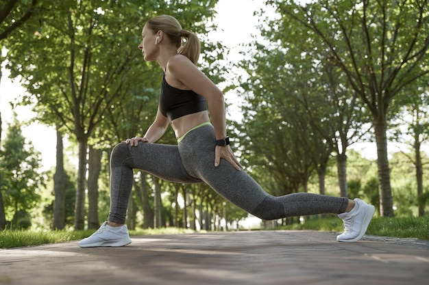 그녀의 다리를 스트레칭 운동복에 아름 다운 피트 니스 여자의 전체 길이 스트레칭 운동을 하 고