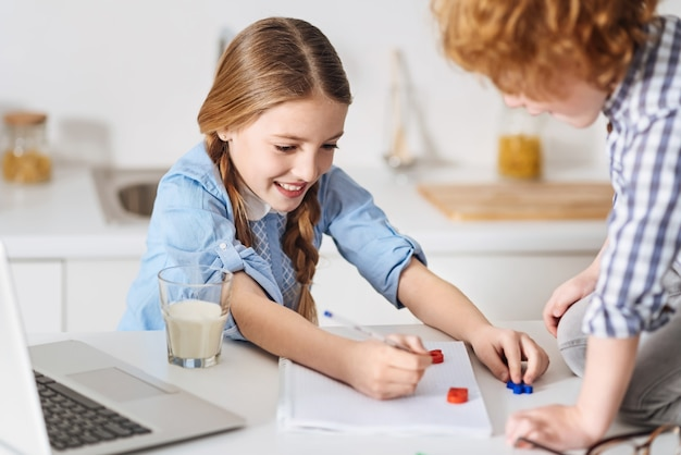 함께 일하기. 귀여운 멋진 빨간 머리 아이가 테이블에 그녀의 오른쪽 옆에 앉아있는 동안 그녀의 수학 과제와 함께 그의 여동생을 돕는 노력