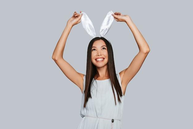 彼女がやりたいことは何でもする。彼女のバニーの耳に触れて、灰色の背景に立って笑っている美しい若いアジアの女性