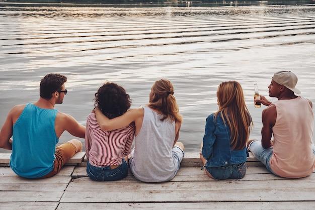 彼らがやりたいことは何でもする。桟橋に座って話しているカジュアルな服装の若者の背面図
