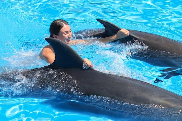 Doiphinsは青い水で幸せな若い女性に乗る。