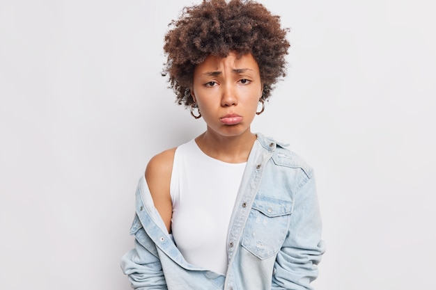 Doleful afro american woman purses lower lip frowns face from something bad makes unhappy grimace being offended dressed in stylish clothes poses against white wall