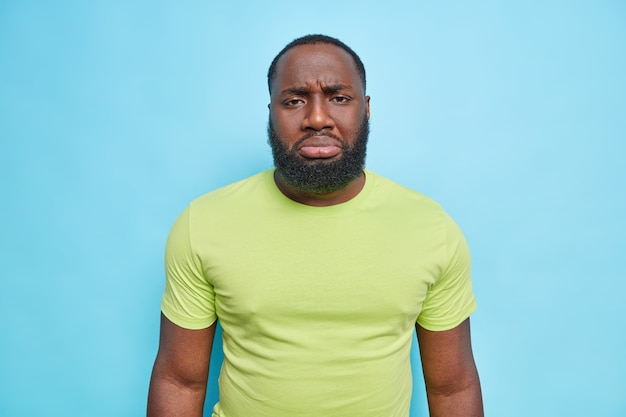 Doleful frustrated bearded adult man with dark skin upset about something frowns face looks displeased at front dressed in casual green t shirt isolated over blue wall