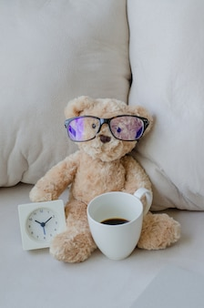 Doll bear and the clock with coffee cup on the Sofa