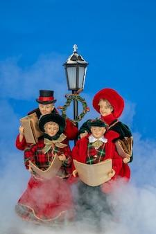 낮에 크리스마스 캐롤을 노래하는 인형 가족. 안개 낀 연기와 밝은 파란색 배경.