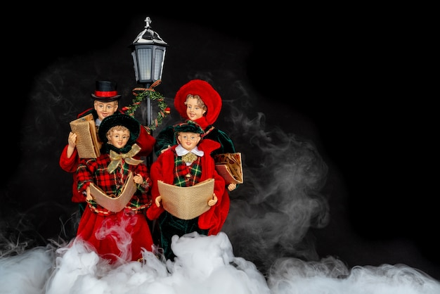 Doll family singing christmas carols in the night with misty smoke.