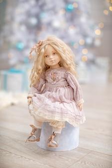 クリスマスツリーの近くのピンクのドレスの人形