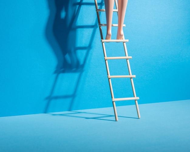 Doll legs on a stepladder on blue.