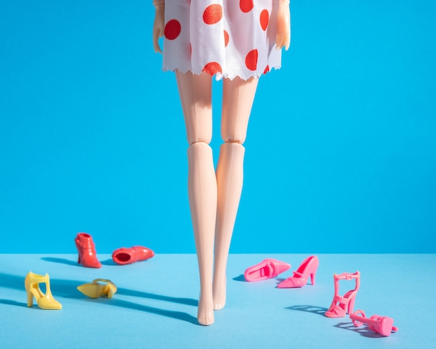 Doll legs with different shoes on a blue.