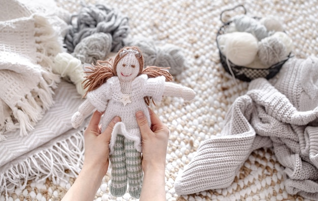 A doll made of knitted elements with threads and yarn in pastel colors.