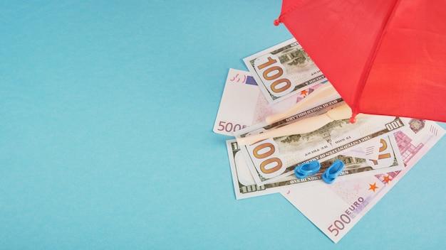 Кукла на деньгах, как на пляжных полотенцах под красным зонтиком, копирование концепции дорогого пляжного отдыха