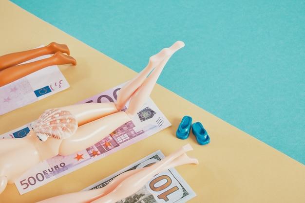 ビーチタオルのようにお金で人形の足、高価な休暇の概念を節約して支払うお金、旅行の概念、青とベージュの背景のコピースペースを節約する