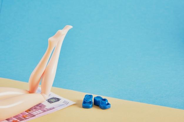 ビーチタオルのようにお金で人形の足、高価な休暇の概念を節約して支払うお金を節約し、旅行の概念のコピースペース