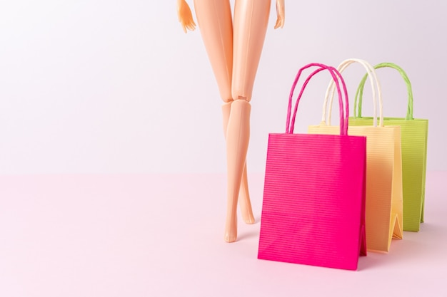 Doll with colorful paper shopping bags on bright background.