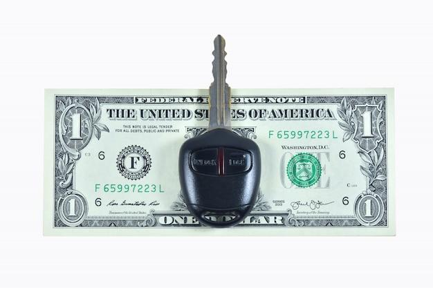 Доллар и ключ автомобиля на белом фоне