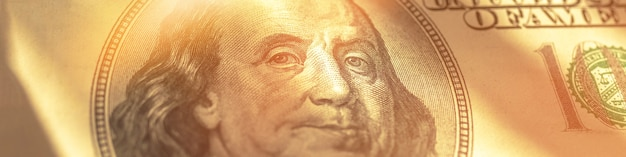 Dollar banknote wide banner, benjamin franklin face in sun rays close-up, business and banking background photo