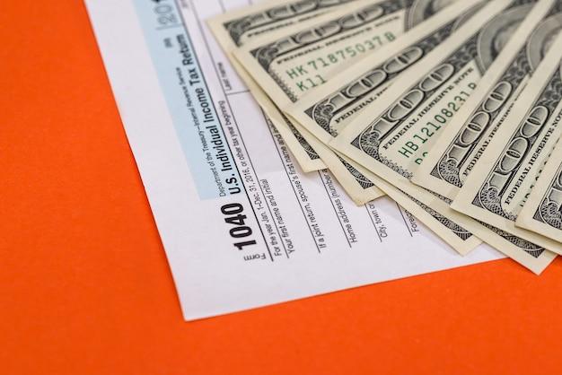 Dollar banknotes on 1040 tax form on orange