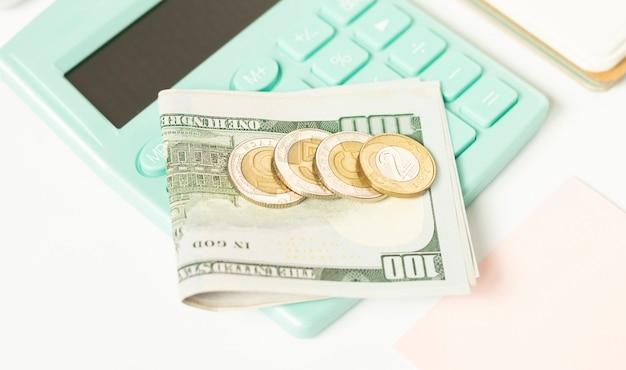 달러 지폐와 황금 동전은 회색과 흰색 버튼이있는 빈티지 계산기 근처 테이블에 누워보기 닫기