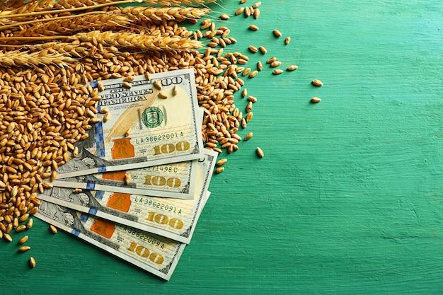 달러 지폐와 컬러 나무 표면에 밀 곡물. 농업 소득 개념