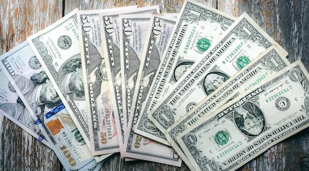 ドル紙幣は、自然なヴィンテージの背景に横たわっています。木の表面にお金のメモ。通貨の切り下げ。ビジネスと社会の問題。