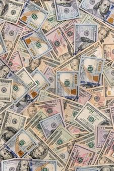 木製のテーブルに散らばったドル紙幣をクローズアップ
