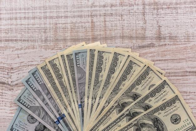 木製のテーブルの上のファンでドル紙幣をクローズ アップ