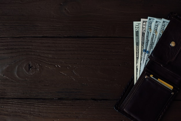 갈색 나무 테이블에 가죽 남자 지갑에서 달러 지폐